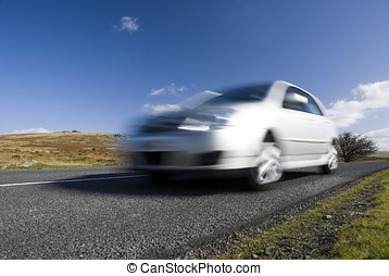 Blurred silver car on mountain road