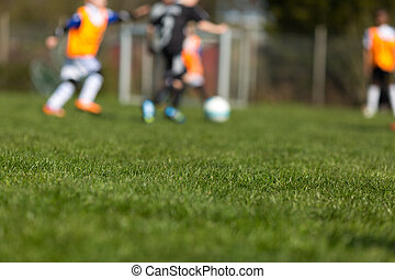 Blurred soccer kids - Blurred kids playing soccer on a sunny...