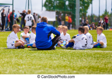 Blurred sports background. Coach giving young soccer team instructions. Youth soccer team together before final game. Football match for children. Boys group shout team, gathering. Coach briefing. Soccer football background.