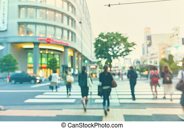 Blurred street intersection in a big city with people