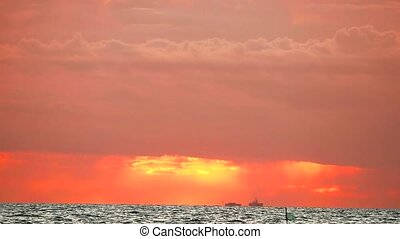 blurred sunset orange sky and red cloud moving and wave on sea
