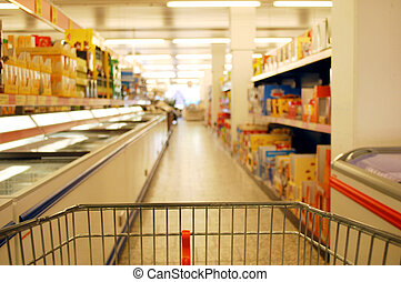 blurred supermarket aisle with focus on shopping cart