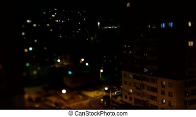 Blurred timelapse clip of night street life. Aerial view of apartment buildings, parking cars and passerby.