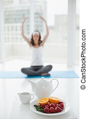 Blurred toned young woman sitting in meditation posture with healthy food in foreground at fitness studio
