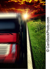 Blurred Truck on asphalt road under storm sky with clouds