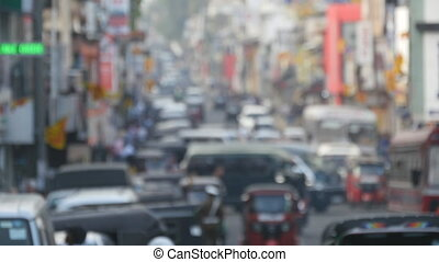 Blurred unrecognizable people are walking around city center. Cars drive on roads in the town. Out of focus is backdrop of bustling big city with busy traffic
