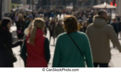 Blurred unrecognizable people walk along sunny spring street slow motion video