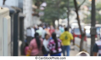 Blurred unrecognizable people walking in city. Pedestrians walking in downtown. Out of focus background from busy big city with people going along street. Slow motion