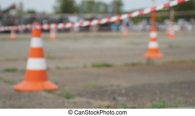 Fencing tape and road cone on the background of passing...
