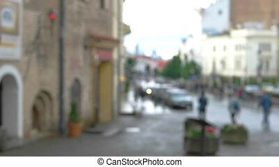Blurred view of a street. People moving in the background....