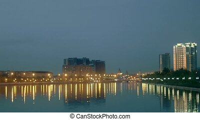 Blurred view of city on a shore. City waterfront in night time with lights of buildings and street lamps