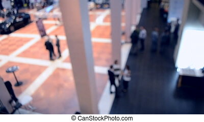 Blurred View of People. People in a large modern hall. Blurred Background.