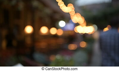 Blurred view of street cafe decorated with light bulbs and people walking by