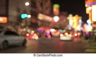 Blurred view of the night street with illuminated red lights in Chinatown at Bangkok