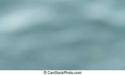 Blurred water background. Defocused sea or ocean surf.