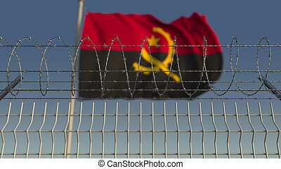 Blurred waving flag of Angola behind barbed wire fence. 3D rendering