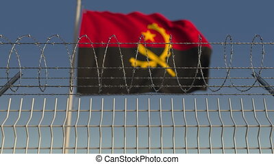 Blurred waving flag of Angola behind barbed wire fence....