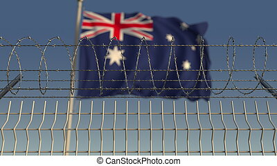 Blurred waving flag of Australia behind barbed wire fence. ...