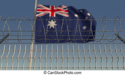 Blurred waving flag of Australia behind barbed wire fence....