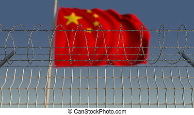 Blurred waving flag of China behind barbed wire fence....