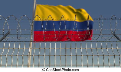Blurred waving flag of Colombia behind barbed wire fence....