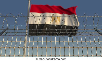 Blurred waving flag of Egypt behind barbed wire fence. 3D ...