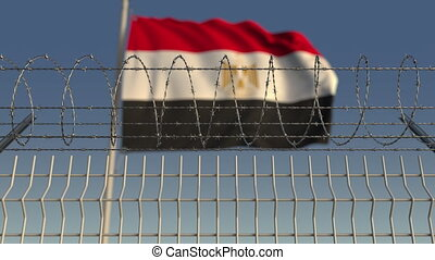 Blurred waving flag of Egypt behind barbed wire fence....