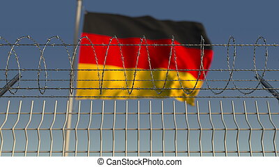 Blurred waving flag of Germany behind barbed wire fence. 3D rendering