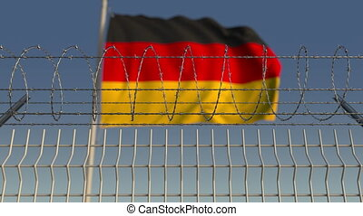 Blurred waving flag of Germany behind barbed wire fence....