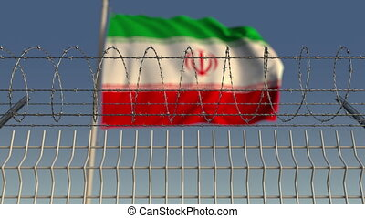 Blurred waving flag of Iran behind barbed wire fence....