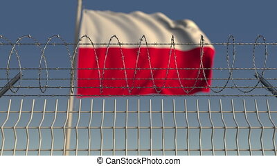 Blurred waving flag of Poland behind barbed wire fence....