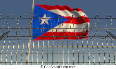 Blurred waving flag of Puerto rico behind barbed wire fence...