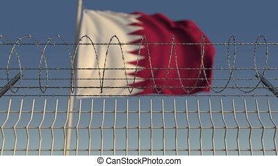 Blurred waving flag of Qatar behind barbed wire fence....