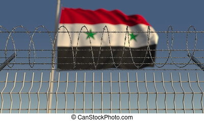 Blurred waving flag of Syria behind barbed wire fence....