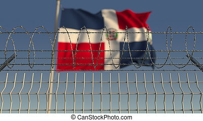 Blurred waving flag of the Dominican Republic behind barbed ...