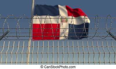 Blurred waving flag of the Dominican Republic behind barbed...
