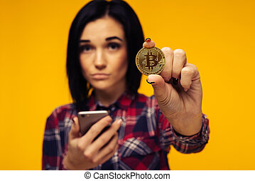 Blurred woman holding a Bitcoin in her hand and showing it - Image