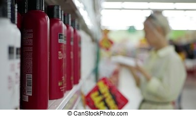 Blurred young woman choosing hair conditioner or shampoo in...