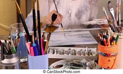 Blurry artist painting - Woman painting with watercolors in...