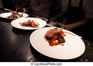 Blurry background of Chef in hotel or restaurant kitchen cooking with lamb and decoration for luxury dinner party.