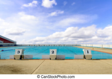 Blurry background swimming start platform with number one two three and blue sky.