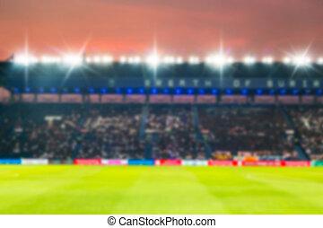 Blurry de-focused stadium football twilight background.