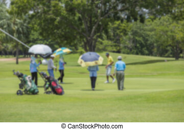 blurry golfers hit sweeping golf course in the summer on sunshine for relax time for background