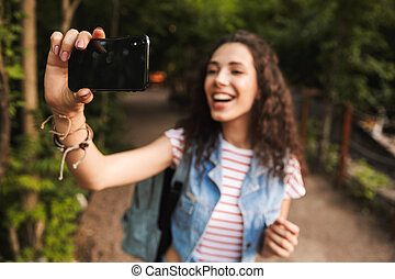 Blurry photo of brunette pretty woman 18-20 with backpack, smiling broadly and taking selfie photo on cell phone while walking along path in green park