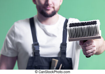 Blurry portrait of a home interior renovation worker holding a big painting brush in focus on a neo mint green wall background