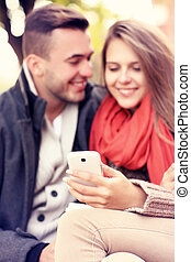 Blurry portrait of a young couple on a bench with smartphone in