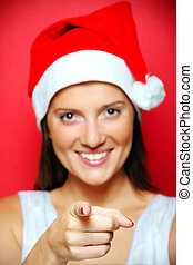 A blurry portrait of Santa's helper pointing at someone over red background, focus on finger