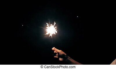Blurry sparkler burning in hand of boy