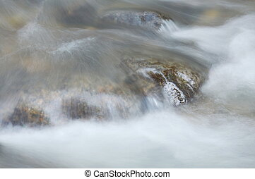 blurry water flowing on the rock and wave splashing in river
