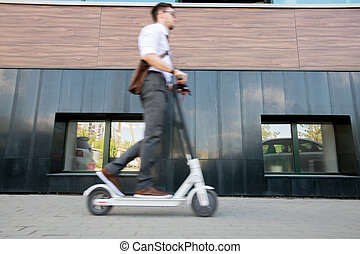 Blurry young businessman on scooter moving forwards along wall of building